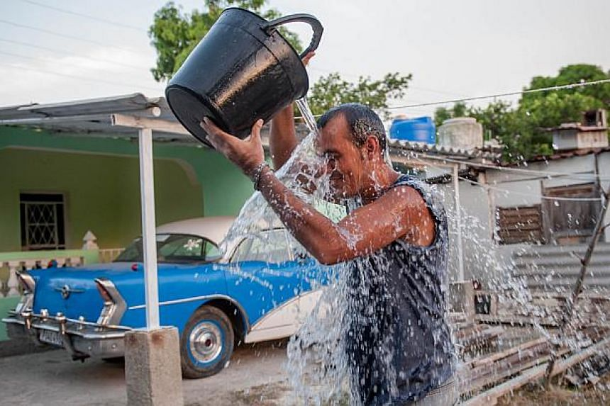 A Cuban man refreshes himself in a street of Havana, in this Aug 27, 2014, file photo. This year may end as the hottest on record, the UN's weather agency said Wednesday as it recounted a tale of rising seas, crippling droughts and floods since