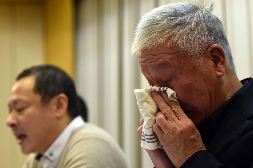 """Pro-democracy activists Benny Tai (left) attends a press conference while Chu Yiu-ming (right) reacts in Hong Kong on Dec 2, 2014. The three original founders of Hong Kong's pro-democracy Occupy movement tearfully announced they would """"surrender"""" by"""