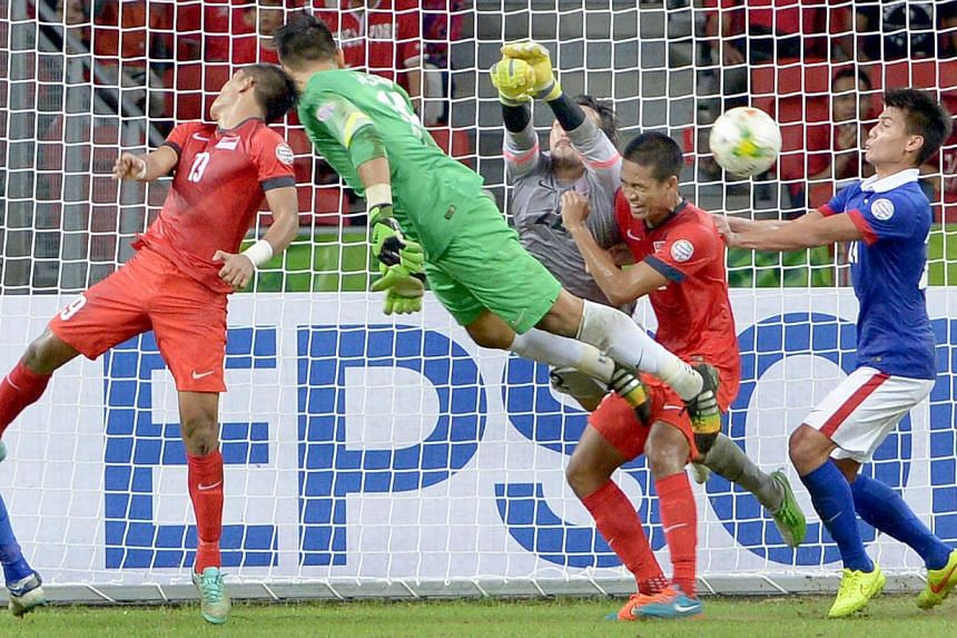 Lions goalkeeper Hassan Sunny (in green) attempting to score the equaliser in his team's AFF Suzuki Cup match against Malaysia at the National Stadium on Nov 29, 2014. -- ST PHOTO: LIM SIN THAI