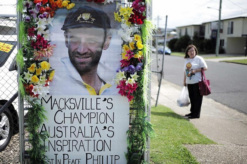 A local resident is pictured alongside a tribute to deceased Australian cricketer Phillip Hughes as his hometown prepares for his funeral in Macksville, on Dec 2, 2014. -- PHOTO: REUTERS