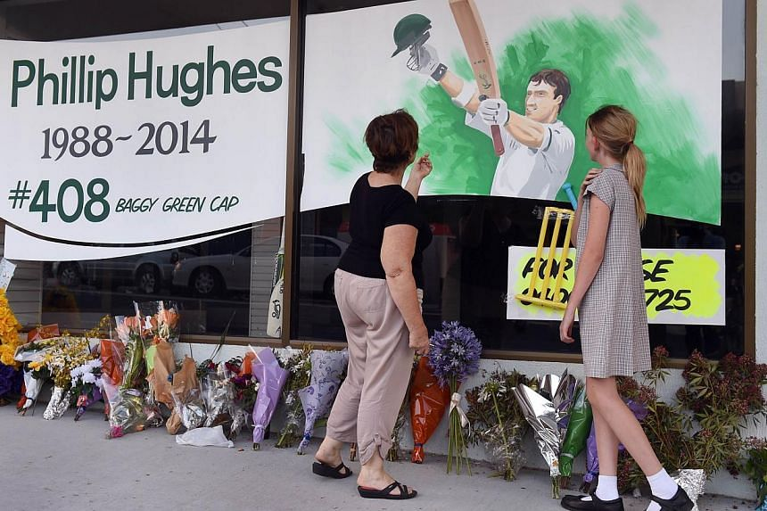 A schoolgirl and her mother inspect a tribute to Australian batsman Phillip Hughes before Hughes' funeral to be held in his hometown of Macksville in northern New South Wales, on Dec 2, 2014. -- PHOTO: AFP