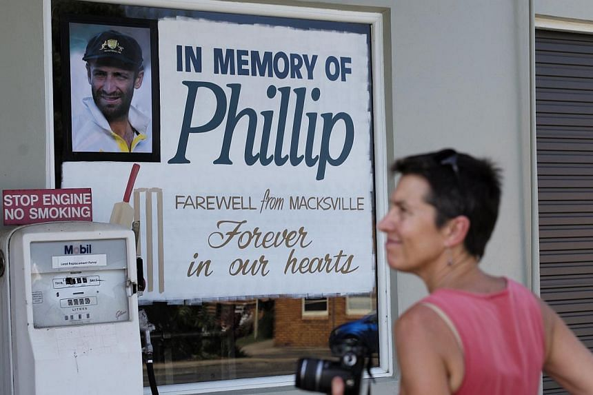 A woman observes a tribute to deceased Australian cricketer Phillip Hughes outside a shopfront in Macksville as his hometown prepares for his funeral, on Dec 2, 2014. -- PHOTO: REUTERS