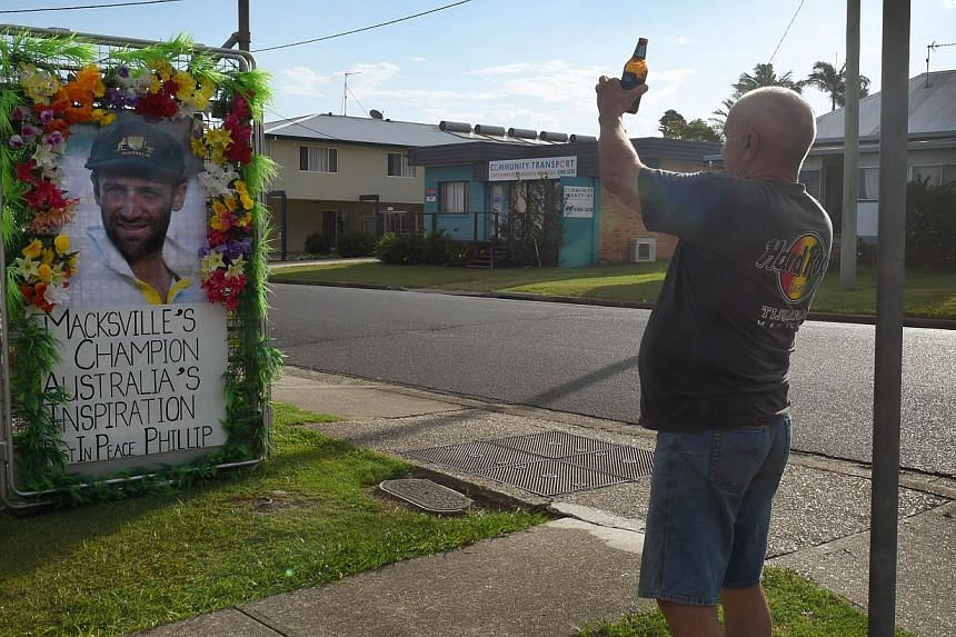 A man holds a beer as he takes a photo of a tribute to Australian batsman Phillip Hughes before Hughes' funeral which will be held in his hometown of Macksville in northern New South Wales, on Dec 2, 2014. -- PHOTO: AFP