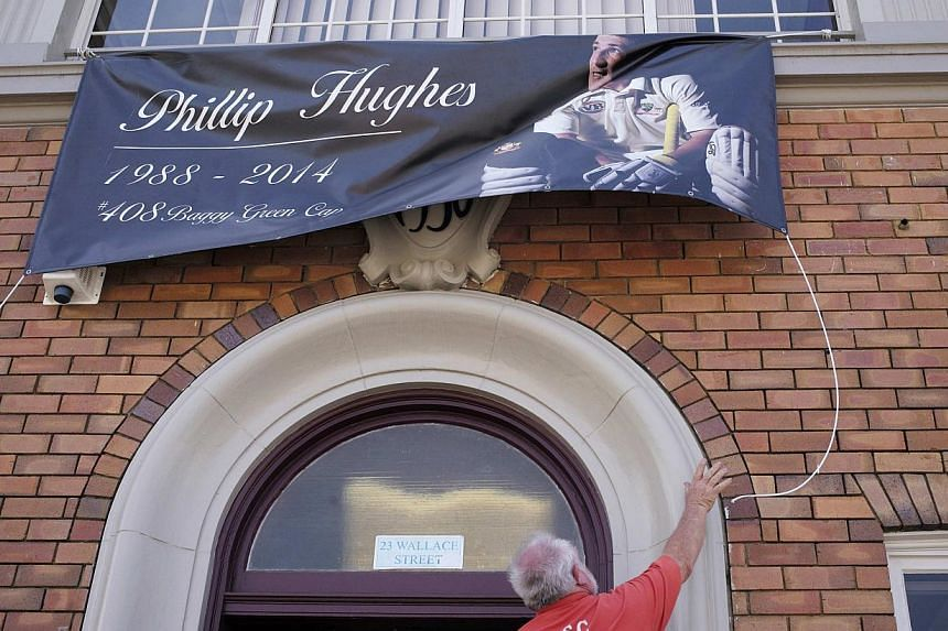 A local resident strings up a banner in honour of Australian cricketer Phillip Hughes in Macksville as his hometown prepares for his funeral, on Dec 2, 2014. -- PHOTO: REUTERS