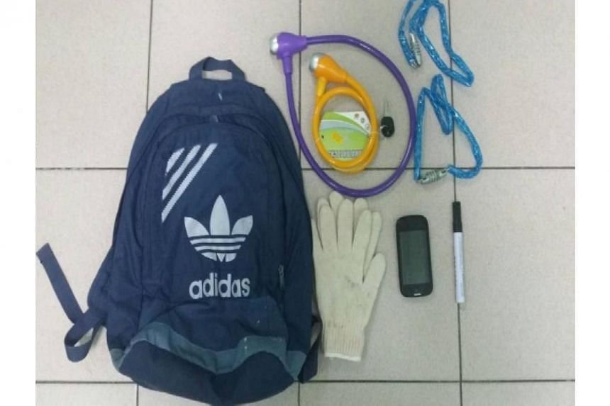 Mobile phone, pair of gloves, marker pen, four bicycle locks seized after arrest on Tuesday of 42-year-old man who is suspected of harassing debtors for a loanshark syndicate. -- PHOTO: SINGAPORE POLICE FORCE