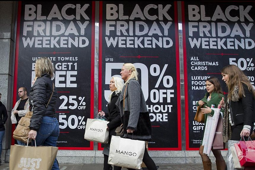 Shoppers are pictured walking past Black Friday advertising in shop windows on Oxford Street in central London on Nov 28, 2014.British department store chain John Lewis and other retailers reported record sales last week as shoppers surged into store