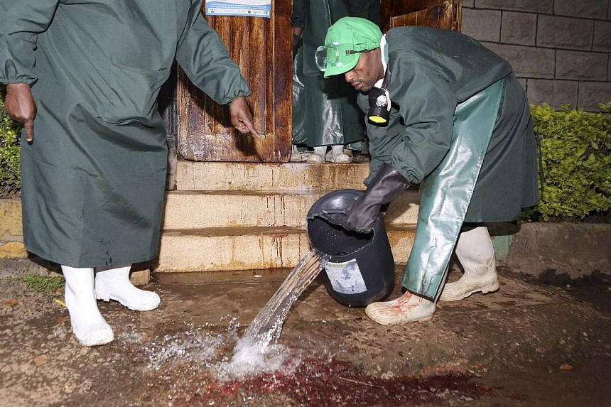 Mortuary workers clean the blood stained floor after receiving the bodies of workers killed at a quarry site in Korome, outside the border town of Mandera, after the bodies were flown to Kenya's capital Nairobi on Dec 2, 2014. Somali al Shabaab Islam