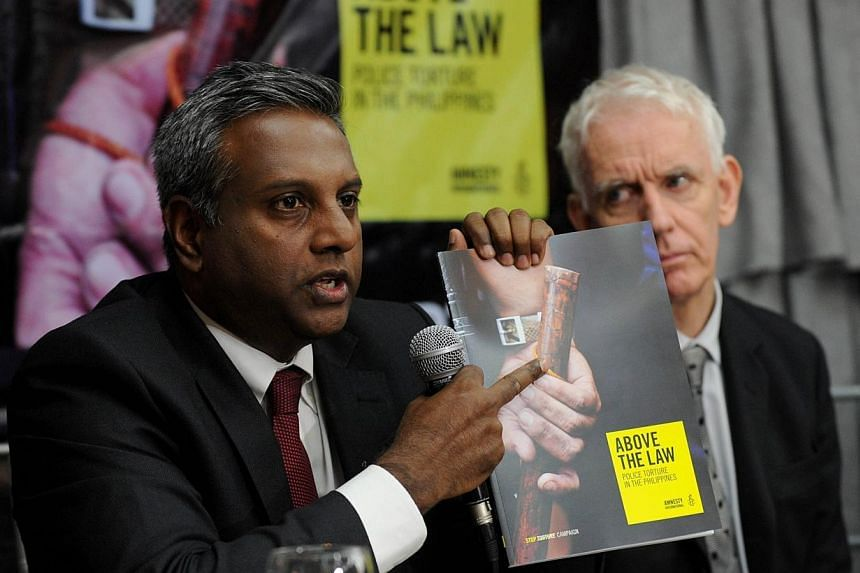 Salil Shetty (left) Amnesty International Secretary-General shows a report of police torture as Steve Crawshaw looks on during the launching of the report of police torture in the Philippines in suburban Manila on Dec 4, 2014. Torture of suspect