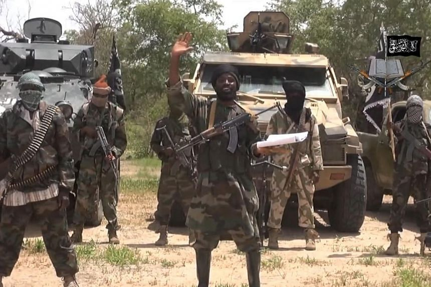A screengrab taken on July 13, 2014 from a video released by the Nigerian Islamist extremist group Boko Haram and obtained by AFP shows leader Abubakar Shekau (centre). The groupraided a cement facility owned by French group Lafarge as part of