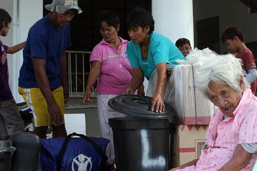 An elderly woman sits while other family members gather their belongings as they arrive at a stadium, serving as a temporary evacuation centre for residents in Tacloban City, central Philippines on Dec 4, 2014, ahead of the arrival of Typhoon Hagupit