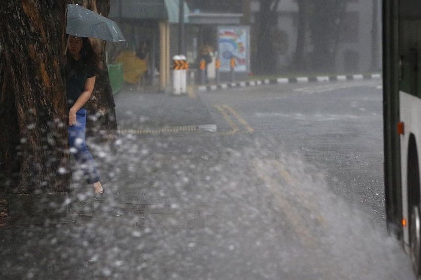 A woman tries to avoid a spout of water caused by a bus along Toa Payoh Lorong 1 on the morning of Dec 4, 2014. -- ST PHOTO: KEVIN LIM