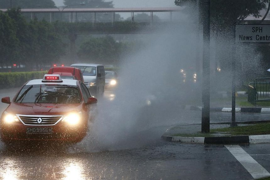 A taxi causes water to splash along Braddell Road on the morning of Dec 4, 2014. -- ST PHOTO: KEVIN LIM