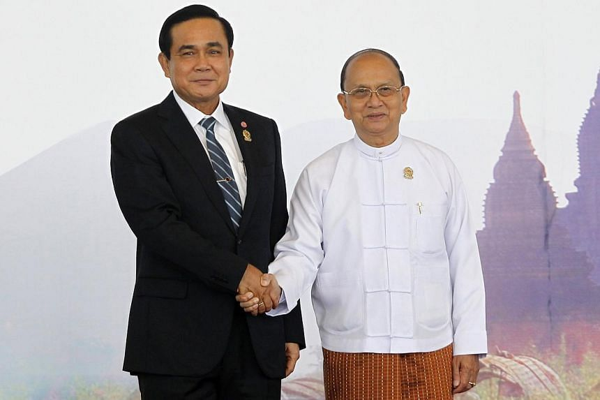 Thailand's Prime Minister Prayuth Chan-ocha shakes hands with Myanmar's President Thein Sein as he arrives for the East Asia Summit (EAS) plenary session during the ASEAN Summit in Naypyitaw on Nov 13, 2014.The two countries will sign a pact in