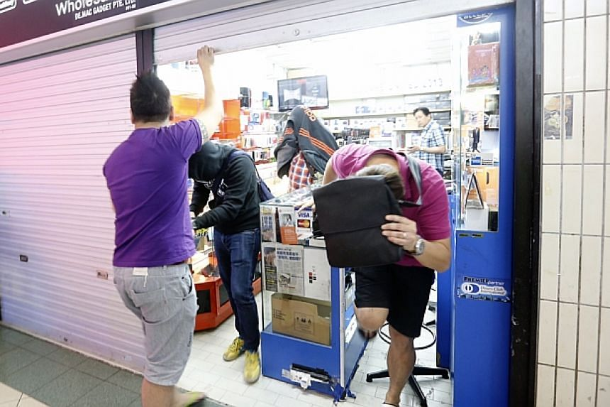 Police conducting a raid at De.Mac Gadget Pte Ltd (#01-50) in Sim Lim Square on Dec 4, 2014. -- ST PHOTO: KEVIN LIM