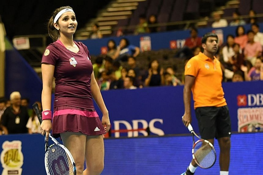 India's Sania Mirza and Rohan Bopanna of the Manila Mavericks play against Canadian Daniel Nestor and Belgium's Kirsten Flipkens during their mixed doubles at the International Premier Tennis League (IPTL) competition in Singapore on Dec 4, 2014. --