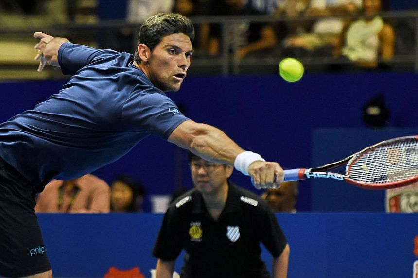 Australia's Mark Philippoussis of the Manila Mavericks plays against France's Cedric Pioline of India Aces during their men's singles at the International Premier Tennis League (IPTL) competition in Singapore on Dec 4, 2014. -- PHOTO: AFP