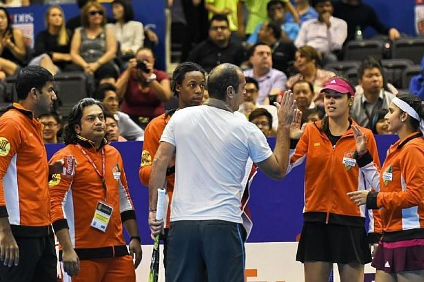 France's Cedric Pioline (centre) of India Aces greets team mates between match against Australia's Mark Philippoussis of the Manila Mavericks during their men's singles at the International Premier Tennis League (IPTL) competition in Singapore on Dec