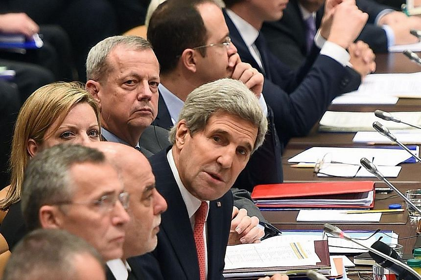 US Secretary of State John Kerry (centre) addressing a meeting of the coalition of around 60 mainly Western and Arab nations in Brussels yesterday. Mr Kerry said ISIS' momentum in Iraq had dissipated.