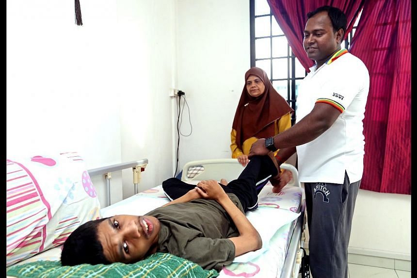 Physiotherapist Gopu Ellappan helping Mr Hasan, who has spastic cerebral palsy, with limb exercises. Mr Ellappan visits the family thrice a week as part of the home-based care services pilot scheme.
