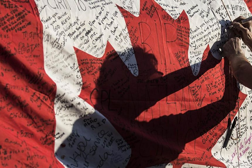A woman writes a message on a Canadian flag at a makeshift memorial in honour of Cpl Nathan Cirillo, outside the Lieutenant-Colonel John Weir Foote Armoury, on Oct 24, 2014. -- PHOTO: REUTERS