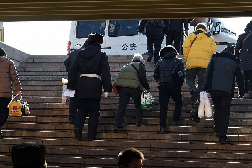 Policemen lead a group of people to a police van in Beijing's Tiananmen Square on Dec 4, 2014. -- PHOTO: AFP
