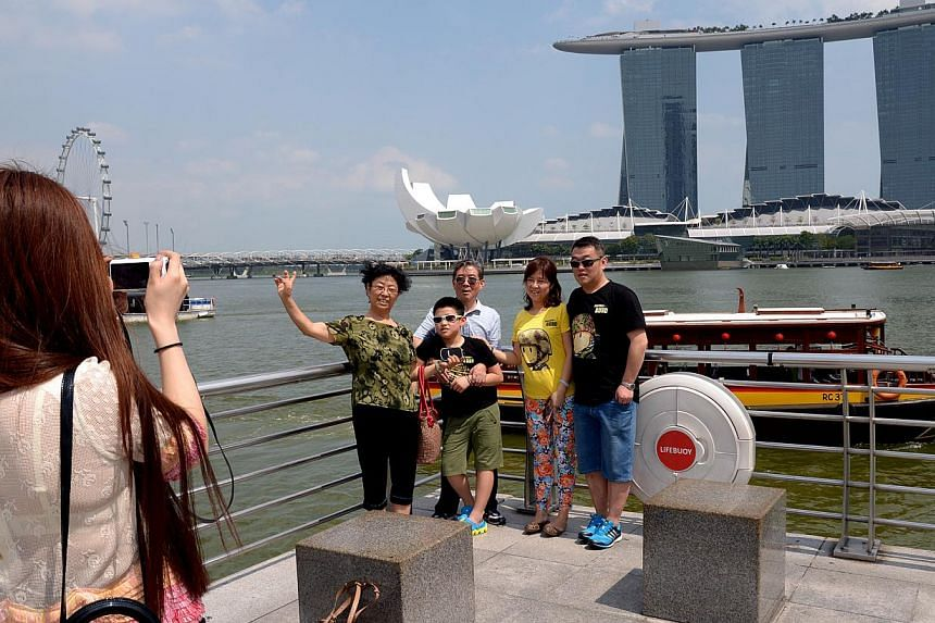 A lady taking a group photograph for tourists from China at Marina Bay. Over a million Chinese tourists made their way to Singapore this year. -- ST PHOTO: LIM SIN THAI