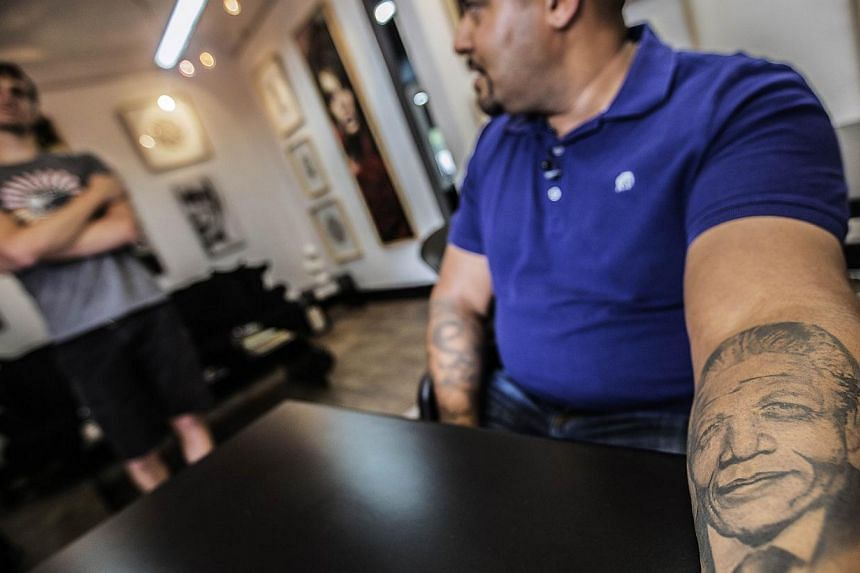 South African businessman Leesha Ramasamy, 42, shows off his tattoo representing Nelson Mandela at the fallen Heroes Tattoo studio on Nov 24, 2014 in Johannesburg, South Africa. Dec 5, 2014 will mark one year since Nelson Mandela, the 95-year-old for