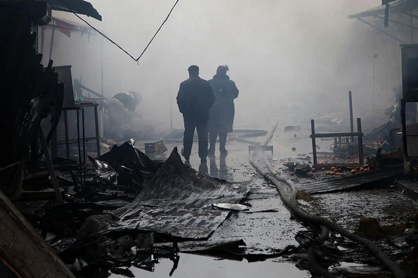 People walk past burnt out kiosks at a street market close to a destroyed building housing the housing the local media known as the Press House, in central Grozny on December 4, 2014. -- PHOTO: AFP