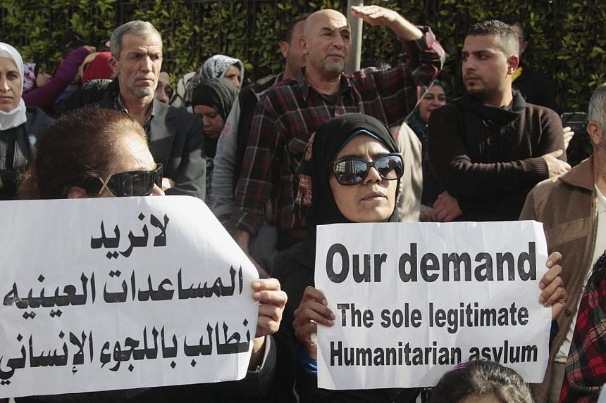 """Palestinians who fled the fighting in Syria carry signs during a protest, asking for help in improving their living conditions and demanding humanitarian asylum, in front of UN offices in Beirut on Dec 4, 2014. The sign (left) reads, """"We don't want a"""