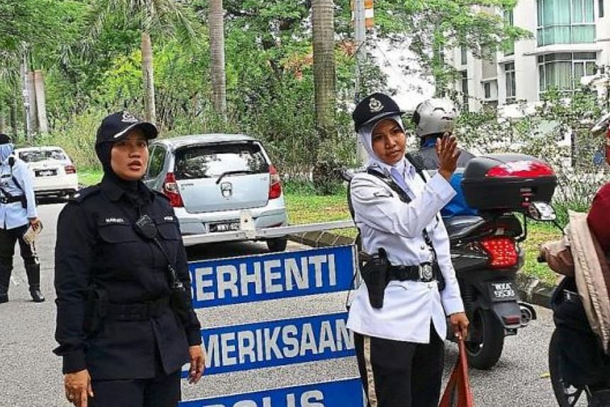 The all-woman police team manning a roadblock in Petaling Jaya. -- PHOTO: THE STAR/ASIA NEWS NETWORK