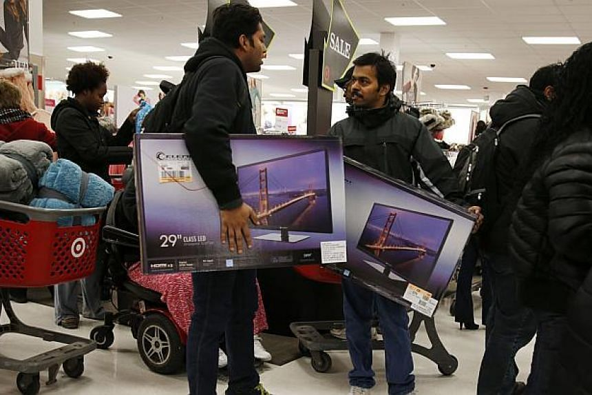 Thanksgiving Day shoppers carry televisions at a Target store in Chicago, Nov 27, 2014. The US economy continued growing in October and November amid widespread optimism about the growth outlook, according to a Federal Reserve report released Wednesd