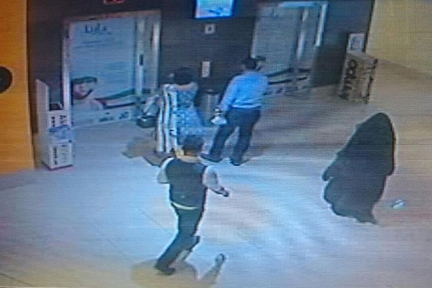 A person (right), dressed in a black robe and suspected in the killing of a US woman at a shopping mall at Al Reem Island in Abu Dhabi is seen in this still image taken from a monitoring camera footage provided by Abu Dhabi Police on Dec 3, 2014. --