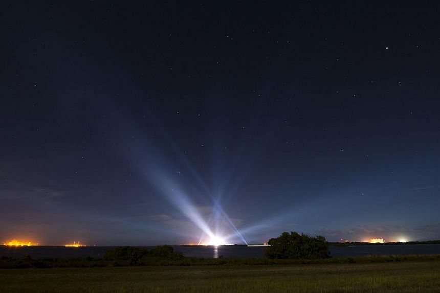 A United Launch Alliance Delta IV Heavy rocket with Nasa's Orion spacecraft mounted atop is seen illuminated in the distance in this long exposure photograph taken early on Thursday, Dec 4, 2014 at Cape Canaveral Air Force Station's Space Launch Co