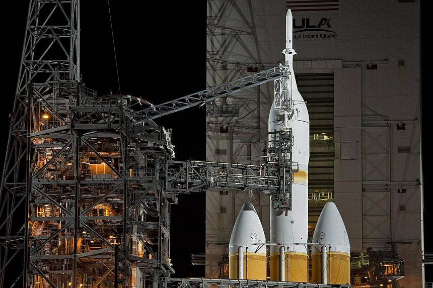 The Mobile Service Tower rolls back from the Delta IV Heavy with the Orion spacecraft on launch pad 37B at Cape Canaveral Air Force Station in Cape Canaveral, Florida on Dec 4, 2014. -- PHOTO: REUTERS