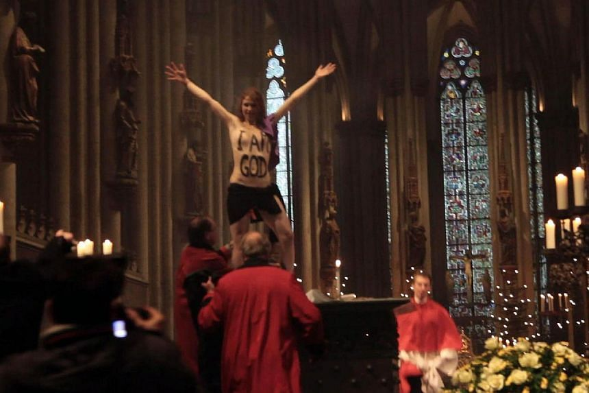 """A picture taken on Dec 25, 2013 shows a topless Femen activist displaying the lettering """"I am God"""" on her chest as she demonstrates during a Christmas Day service at the Cologne Cathedral in Cologne, western Germany.A German court Wednesday han"""