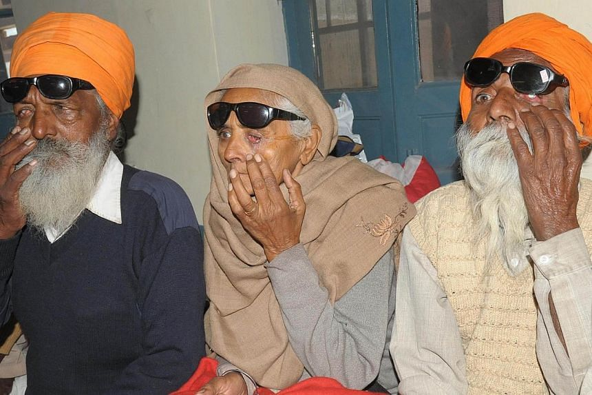 Indian patients Joginder Singh (left), Payar Kaur (centre) and Joginder Singh, who lost their eyesight after undergoing surgery at an eye camp, show their damaged eyes as they sit at a government hospital in Amritsar on Dec 5, 2014.At least 11