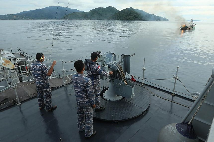 Indonesian Navy officers (left) target a Vietnam boat fishing held due to illegal fishing activities in Indonesia water on Anambas island, Riau province on Dec 5, 2014. -- PHOTO: AFP