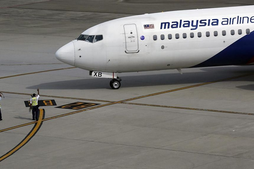 Ground staff wave to a Malaysian Airlines aircraft as it leaves Kuala Lumpur International airport in Sepang outside Kuala Lumpur on Nov 17, 2014.Malaysia Airlines said its shares will be suspended from the country's stock exchange on Dec 15 un