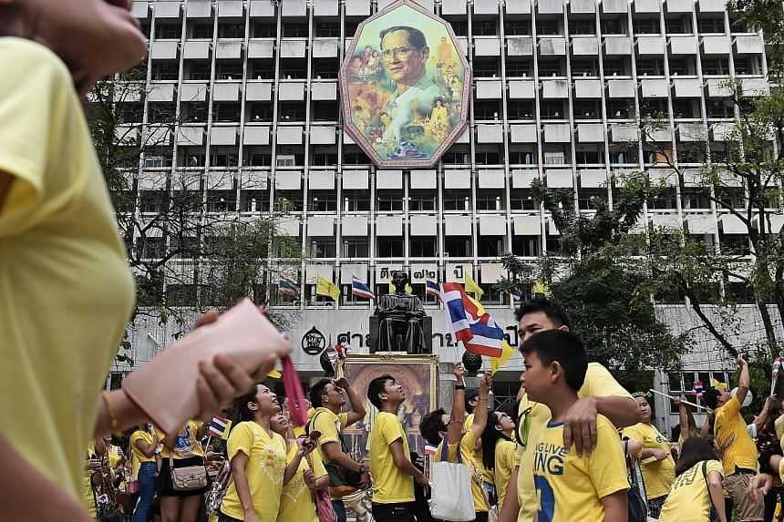 Thai well-wishers try and get a glimpse of King Bhumibol Adulyadej as they gather at Siriraj Hospital where the king has spent most of the last few months, on the occasion of his 87th birthday in Bangkok on Dec 5, 2014. Thailand's ailing King Bh