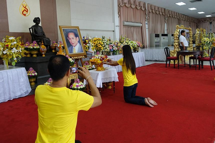 Well-wishers paying their respects before a giant portrait of the Thai monarch in a hall in Bangkok's Siriraj Hospital. King Bhumibol Adulyadej is convalescing in the hospital, where he lived between 2009 and last year. -- ST PHOTO: TAN HUI YEE