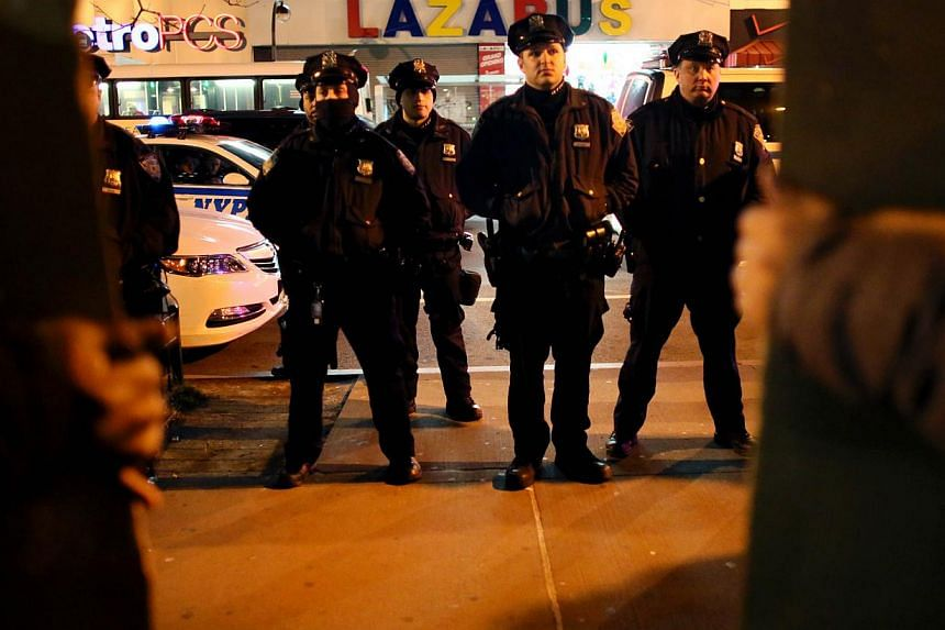Police watch people gather in front of the Adam Clayton Powell Jr. State Office Building during a protest against police killings of black suspects on Dec 4, 2014 in New York City. -- PHOTO: AFP