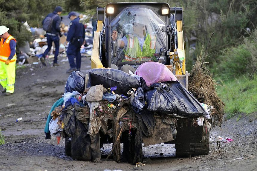 A bulldozer carries debris at a Silicon Valley homeless encampment known as The Jungle on Dec 4, 2014, in San Jose, California. Authorities began dismantling the homeless camp in the heart of California's affluent Silicon Valley. Municipal workers mo