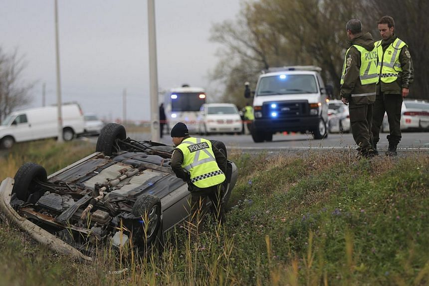 """Officers investigate an overturned vehicle in Saint-Jean-sur-Richelieu, Quebec Oct 20, 2014. A 15-year-old boy charged with seeking to travel abroad to engage in """"terrorist activity"""" is said to have befriended the suspect in the first Islamic extremi"""