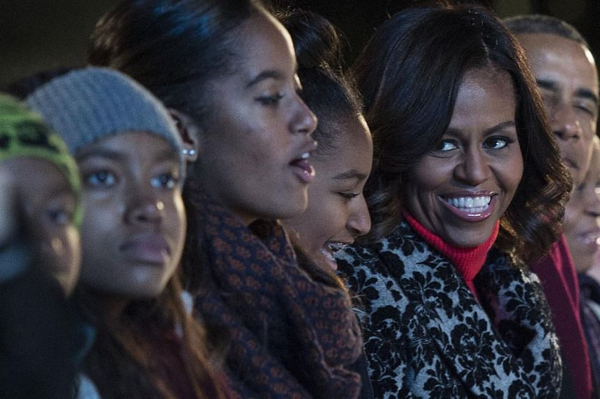 US First Lady Michelle Obama looks to her daughters Malia (left) and Sasha singing during the annual National Christmas Tree Lighting ceremony on the Ellipse in Washington, DC on Dec 4, 2014. -- PHOTO: AFP