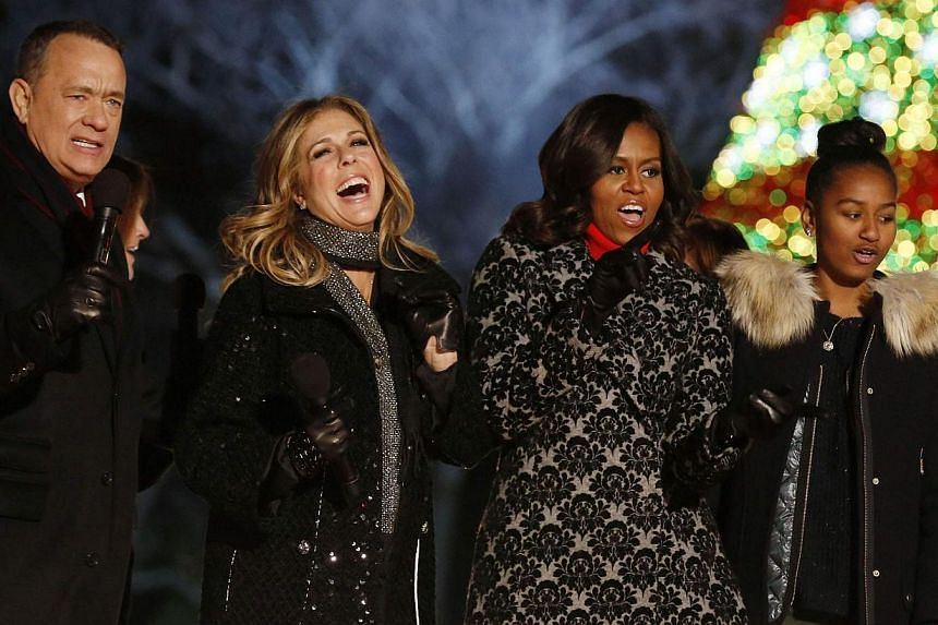 First lady Michelle Obama (second from right) sings with her daughter Sasha and actors Tom Hanks (left) and Rita Wilson (second from left) after the official lighting of the National Christmas Tree on the Ellipse near the White House in Washington, D