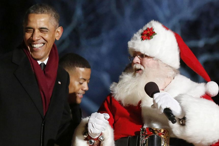 US President Barack Obama smiles on stage next to a man dressed as Santa Claus after he officially lights the National Christmas Tree on the Ellipse near the White House in Washington, DC on Dec 4, 2014. -- PHOTO: REUTERS