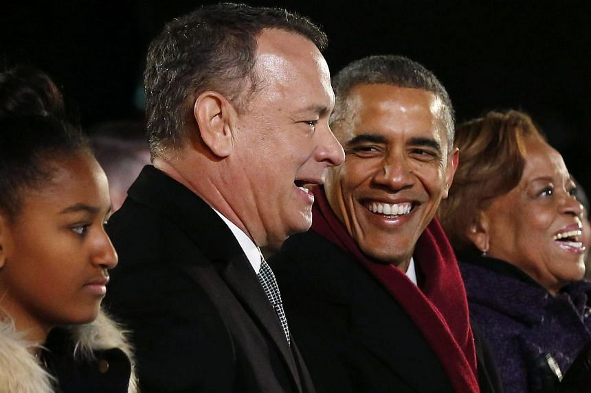 US President Barack Obama (second from right) sits with daughter Sasha (left), mother-in-law Marian Robinson (right) and actor Tom Hanks as they attend the lighting of the National Christmas Tree on the Ellipse near the White House in Washington, DC