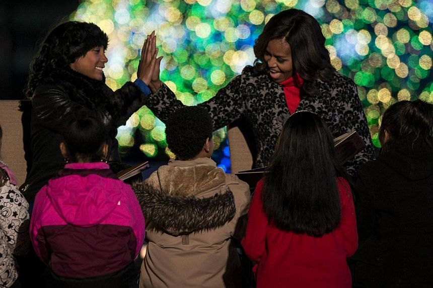 US First Lady Michelle Obama (right) and little league baseball pitcher Mo'ne Davis high-five after reading The Night Before Christmas during the 92nd annual National Christmas Tree Lighting Ceremony on the National Mall's Ellipse in Washington, DC o