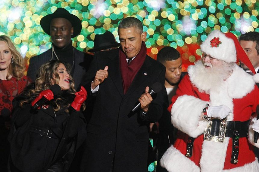 US President Barack Obama (centre) dances with participants during the 92nd annual National Christmas Tree Lighting on the Ellipse near the White House in Washington, DC on Dec 4, 2014. -- PHOTO: REUTERS