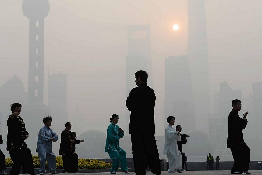 Residents exercising amid heavy smog on the Bund in Shanghai as local meteorological department issued a yellow alert for smog on Nov 12, 2014. -- PHOTO: AFP